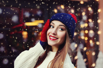 Street portrait of smiling beautiful young woman wearing classic winter knitted clothes. Model looking aside. Festive  garland lights. Magic snowfall effect. Close up. Toned