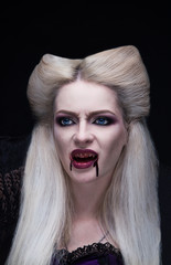Beautiful blonde girl vampire is angry. The blood is on the mouth.