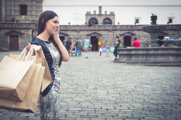 Classy attractive brunette wearing black white dress in urban environment carrying shopping bags and smiling