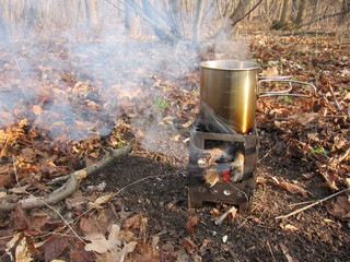 Steel mug of boiling water on the tourist mini stove in the autumn forest