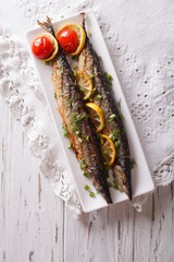 saury grilled with vegetables on a plate. vertical top view