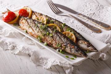 saury grilled with vegetables on a plate. horizontal