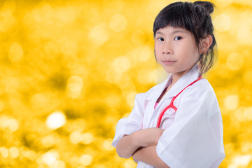 Little girl pretending to be a doctor on yellow bokeh blurry bac