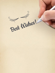 """Hand writing """"Best Wishes!"""" on aged sheet of paper."""