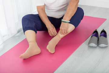 Close up Senior woman sitting on yoga mat during on exercising a