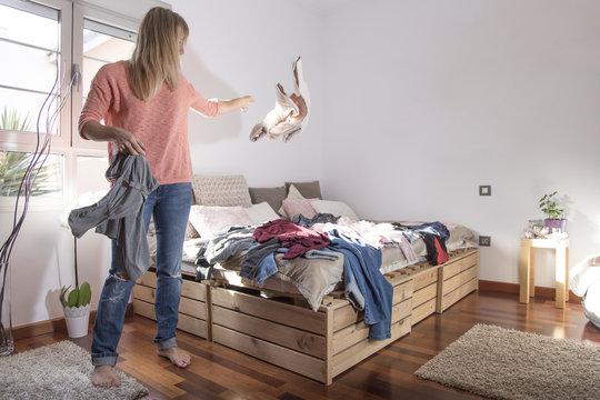 blonde Frau wirft Kleidung auf das Bett
