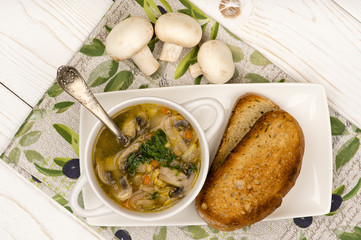 Mushroom soup with roasted bread on the wooden background.