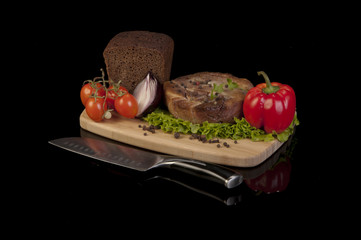 Tasty meat medallion with lettuce, onion, pepper, tomatoes and a loaf of bread on a wooden cutting board. Black background with reflection underneath