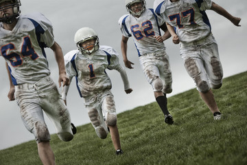 A group of four football players, young people in sports uniform and protective helmets running forward.