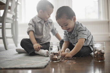 Two boys playing with coins, dropping them into glass jars