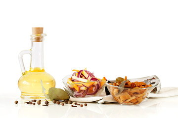 Olive oil, delicious marinated mushrooms and salad with fresh onion and vegetables in glass plate in glass bowls on white background