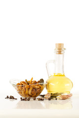 Olive oil and delicious marinated mushrooms in glass bowl, red onion, garlic and spices on white background