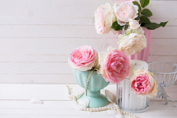 Sweet pink roses flowers in vases and candle on white painted wo