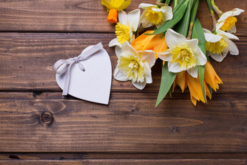 Background with fresh daffodils and tulips and decorative heart
