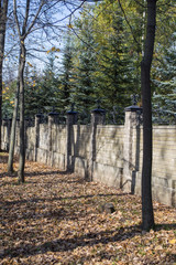 The autumn wood and stone fence with columns