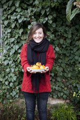 woman holding a dish full of  freshly harvested persimmons in front of a wall covered with ivy leaves