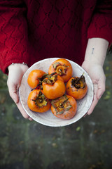 person holding a dish full of freshly harvested persimmons
