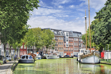 Green canal with moored yachts and apartment buildings, Gouda, Netherlands.