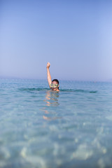 Portrait of smiling girl in swimming mask against the sea and sk