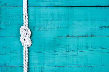 White rope with knot on blank antique teal blue rustic wooden background