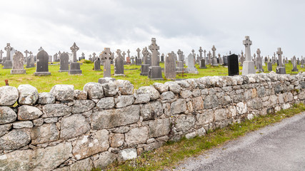 Cemetery and Irish crosses behind a stone wall on an overcast day,  Connemara, Galway, Ireland