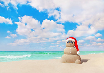 Smiling sandy Snowman in Christmas Santa hat on tropical beach
