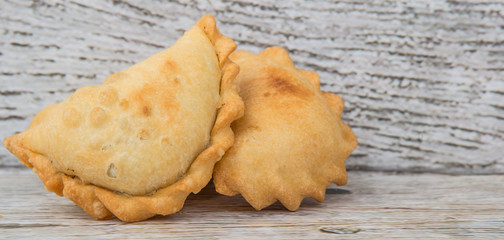 Malaysian popular snack curry puff, locally known as karipap over wooden background