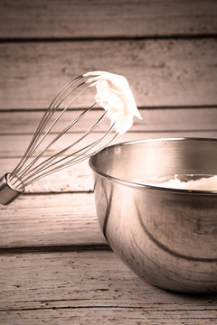 Whisk and bowl with whipped cream
