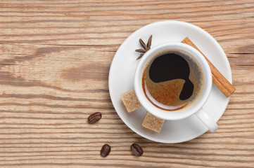 White saucer and cup of coffee espresso decorated cinnamon stick, star anise, cane sugar and coffee beans on rustic wooden table top view with place for text
