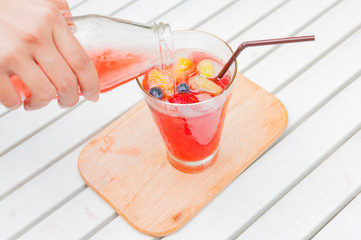 Self pouring ice tea serve with ice cube with fruits frozen insi