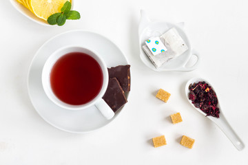 Cup of tea with cube sugar and chocolate on a white table.Top view.