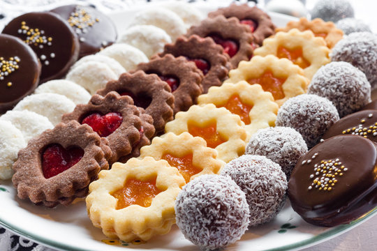 Mixed christmas cookies on a white plate.