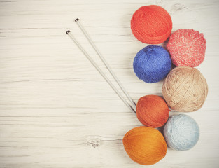 Vintage toned yarn balls on wooden boards.