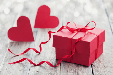 Gift box with red bow ribbon and two paper heart on wooden background for Valentines day