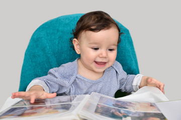 Cute smiling baby girl looking at the photo album