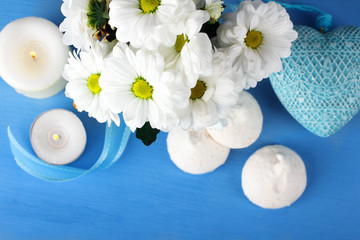 a bouquet of white daisies with candles and sweets around decorative hearts on a blue wooden table