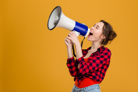 Funny excited young woman shouting in megaphone