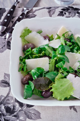 Mesclun salad with olives and Сheese in white salad bowl.