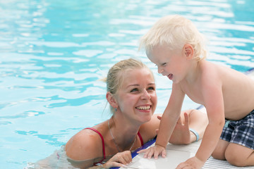 Mother and son have fun by a swimming pool