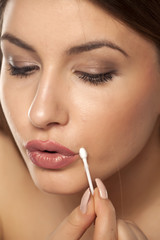 young woman fixes lipstick on her lips with a cotton swab