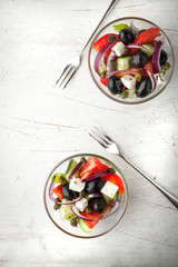Greek salad in the glass dish top view