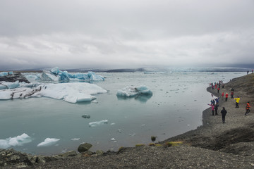 Blue ice at glacier lagoon and black beach on Iceland, summer