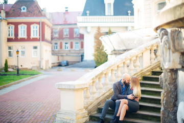 One beautiful stylish couple of young woman and senior man with long black beard sitting embracing close to each other outdoor in autumn street on stairs sunny day, horizontal picture