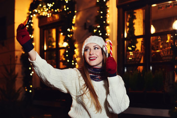 Night street portrait of a smiling beautiful young woman making selfie photo with her smartphone. Festive Christmas background. Toned