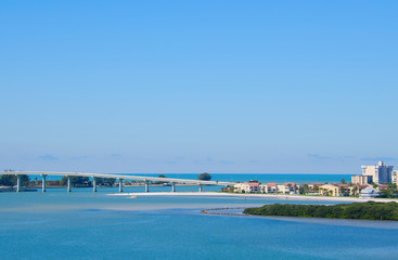 Sand Key Bridge in Clearwater Beach, Florida which crosses Clearwater Pass that leads out to the Gulf of Mexico on a beautiful sunny morning with clear blue skies.