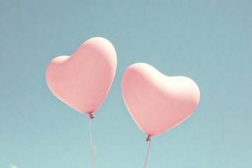 Two pink heart shaped balloons in turquoise sky