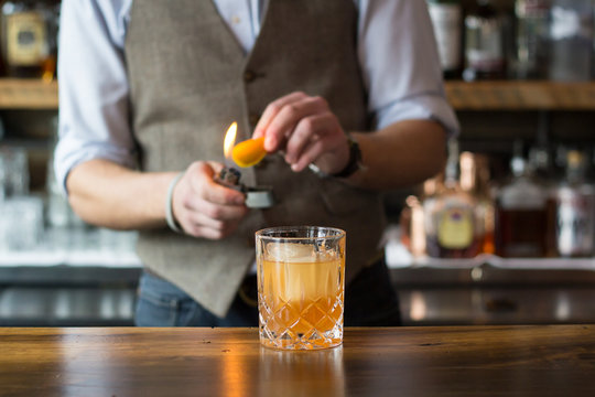 Bartender Flaming an Orange Peel for a Cocktail