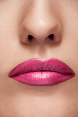 Lips with pink lipstick in close up photo