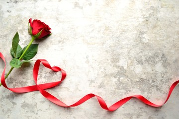 A single red rose with heart shaped red ribbon