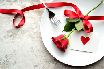 A single red rose with red heart message card on the white dish